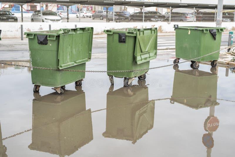 3 больших зеленых пластиковых ненужных ящика на колесах отраженных в лужице дождя на улице стоковые изображения rf