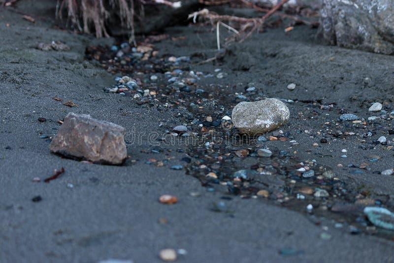 2 больших утеса около тонкой струйки воды с камешками стоковые фото