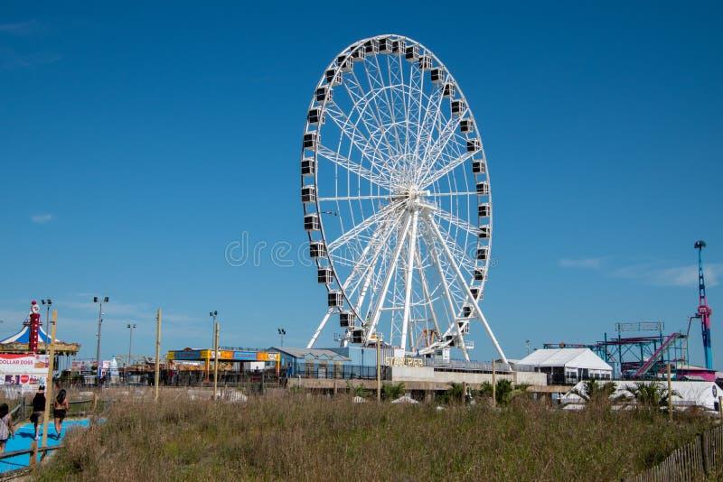 Большое белое колесо ferris с много закрытых отсеков на стальной пристани в Атлантик-Сити, Нью-Джерси увиденном от дюн пляжа стоковое изображение rf