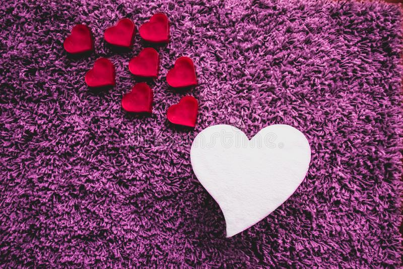 Большое белое сердце с более небольшими розовыми сердцами идя вверх Пурпуровая предпосылка стоковое фото rf