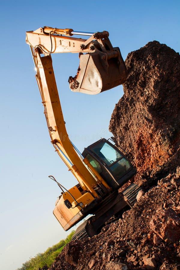 Большое железное ведро экскаватора собирает и льет щебень и камни песка в карьере на строительной площадке объектов дороги стоковая фотография