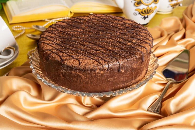 Большое кристаллическое блюдо с тортом губки шоколада на silk скатертях стоковая фотография