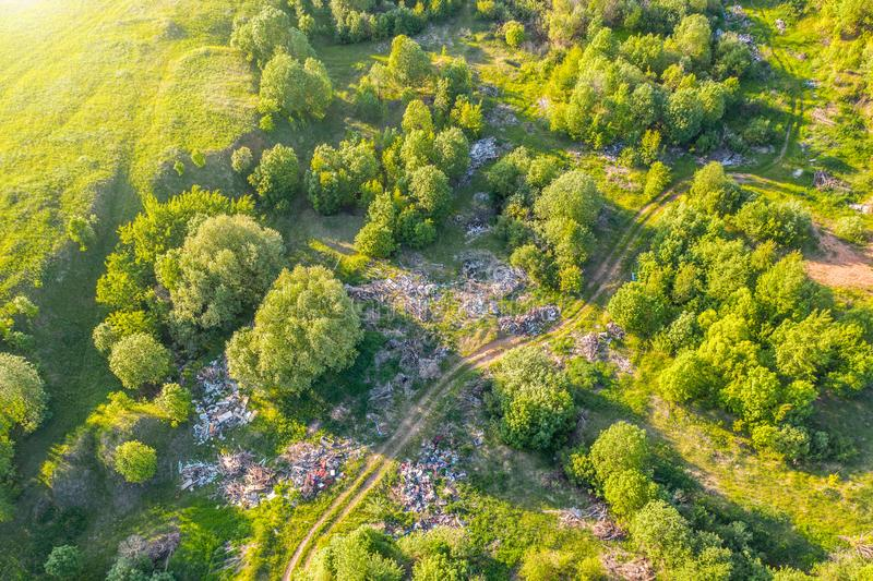 Большое место захоронения отходов отброса, отхода домочадца, пластмасс и других вещей среди зеленого леса вдоль лугов и дороги стоковое изображение