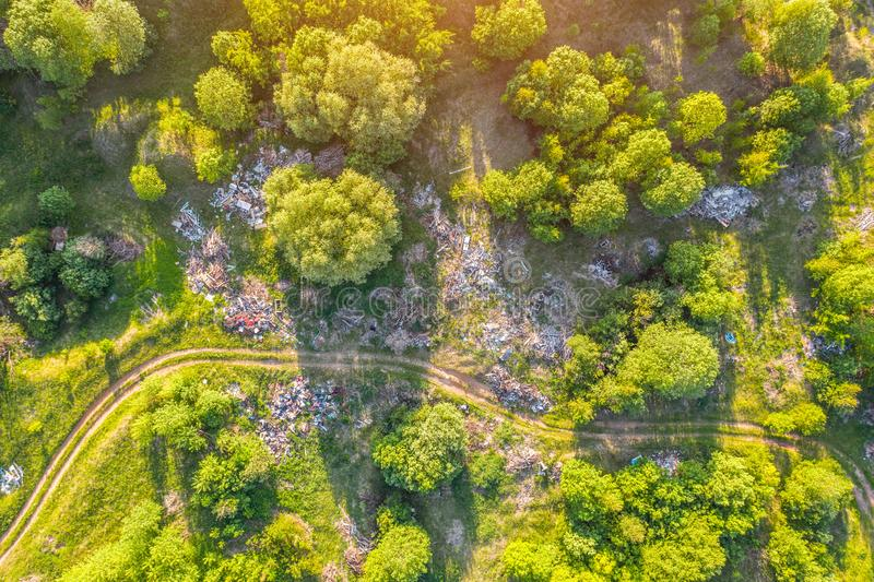 Большое место захоронения отходов отброса, отхода домочадца, пластмасс и других вещей среди зеленого леса вдоль лугов и дороги стоковая фотография