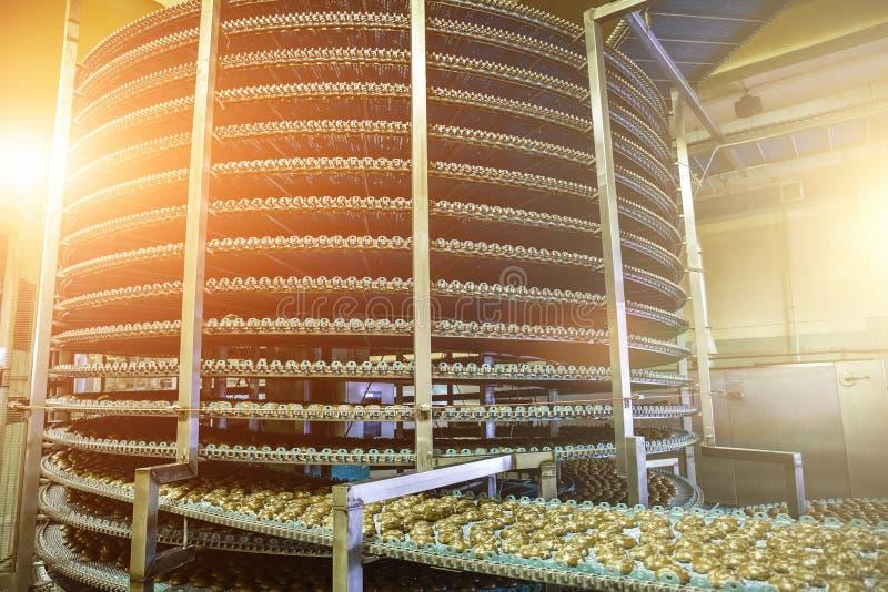 Большое промышленное автоматизированное вокруг линии транспортера или машины пояса в продукции фабрики, печений и тортов еды хлеб стоковые фотографии rf