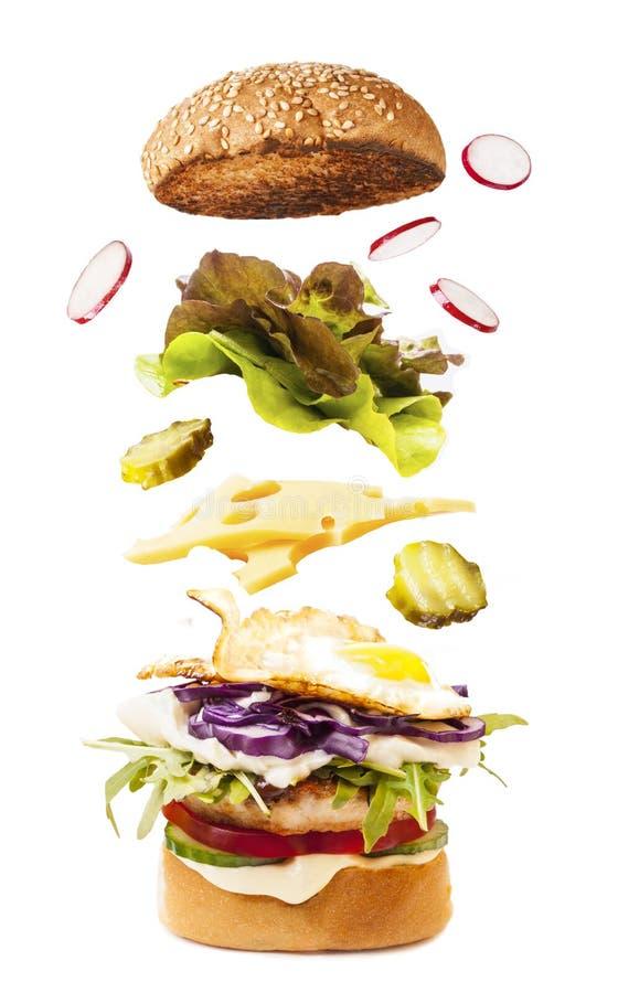 Большой вкусный домодельный бургер с ингридиентами летания стоковая фотография