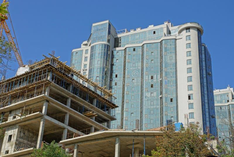 Большой высокорослый дом с стеклянными стенами и незаконченное здание с краном башни стоковые фотографии rf