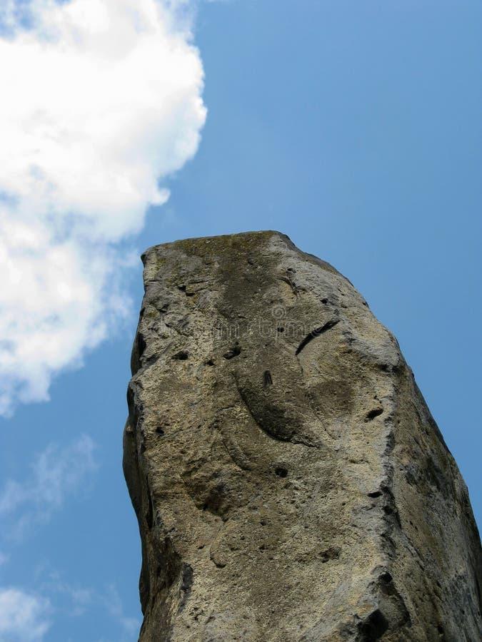 Большой высокорослый камень против голубого неба с белыми пушистыми облаками стоковое фото