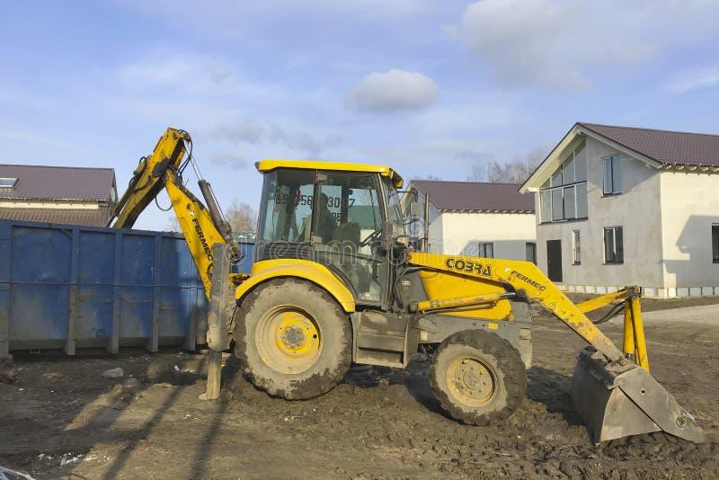 Большой желтый трактор нагружает отброс конструкции в контейнер с ведром стоковые фотографии rf
