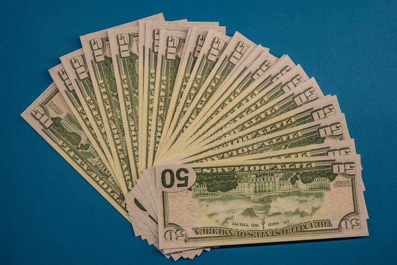 Большой жирный крен денег изолировал на голубой предпосылке стоковая фотография