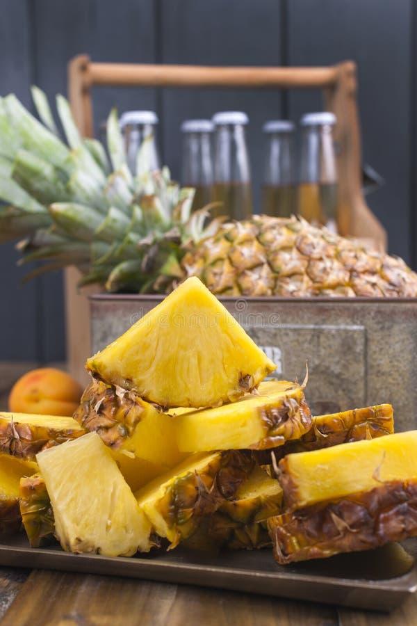 Большой и зрелый ананас отрезан в части, и весь плодоовощ Тропический плодоовощ на деревянной предпосылке и коробка с закруткой д стоковая фотография rf