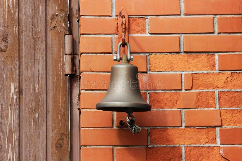 Большой колокол рядом с дверью, заменяя дверной звонок гостеприимсво колокола женщина rwith кольца руки колокола стоковые изображения rf
