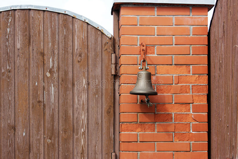 Большой колокол рядом с дверью, заменяя дверной звонок гостеприимсво колокола женщина rwith кольца руки колокола стоковая фотография rf