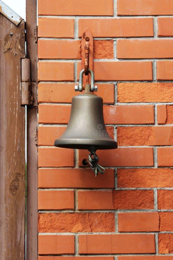 Большой колокол рядом с дверью, заменяя дверной звонок гостеприимсво колокола женщина rwith кольца руки колокола стоковое фото rf