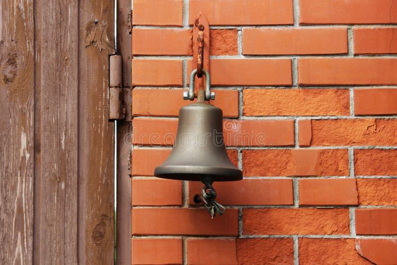 Большой колокол рядом с дверью, заменяя дверной звонок гостеприимсво колокола женщина rwith кольца руки колокола стоковое изображение rf