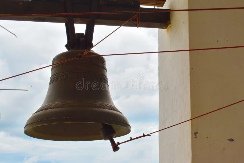 Большой колокол чугуна в колокольне в церков стоковая фотография