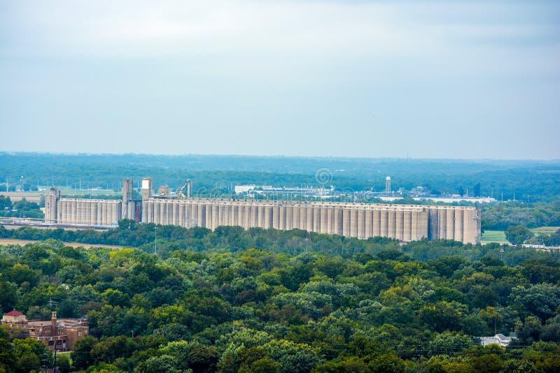 Большой комплекс силосохранилища лифта зерна земледелия с зелеными деревьями стоковое изображение