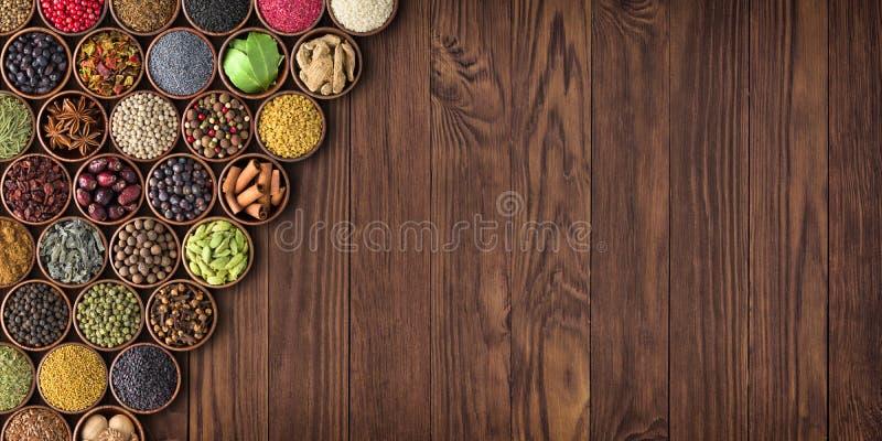 Большой комплект специй на деревянном столе, взгляд сверху стоковые фото