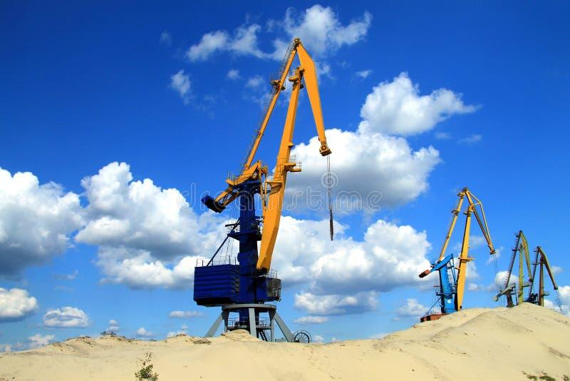 Большой кран башни стоит в речном порте около горы песка на предпосылке красивых облаков стоковые изображения rf
