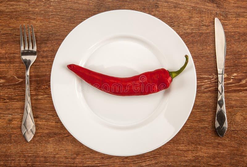 Большой красный пеец на белой плите с kitchenware на таблице стоковая фотография rf