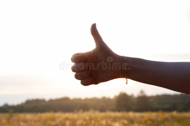 Большой палец руки вверх на заходе солнца стоковое изображение