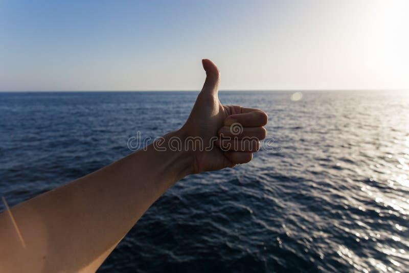 Большой палец руки вверх на море метка утверждения рука жестов стоковое фото rf