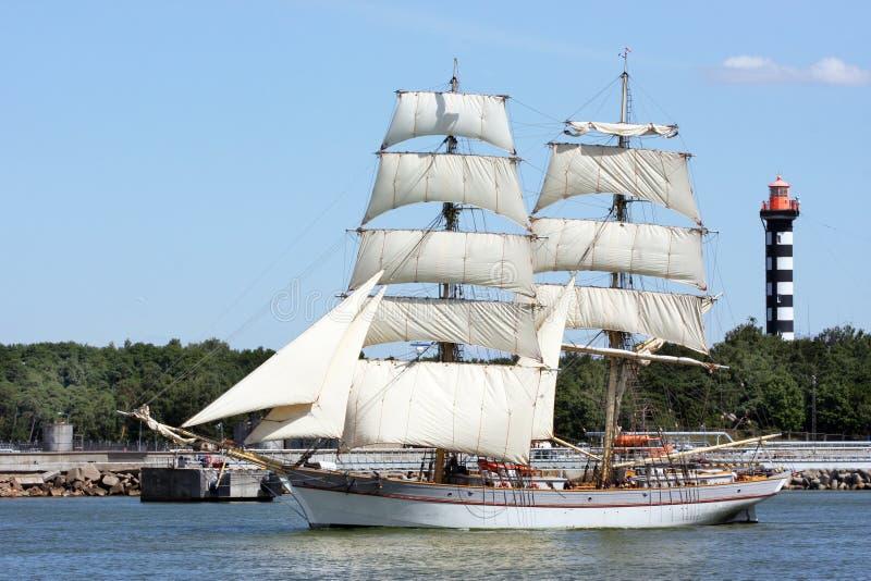 Большой парусник с ветрилами выходит портовая зона стоковое изображение