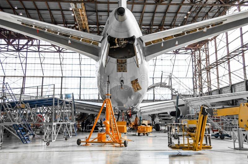 Большой пассажирский самолет на обслуживании в вид сзади ангара авиации кабеля, на вспомогательном источнике питания стоковая фотография rf