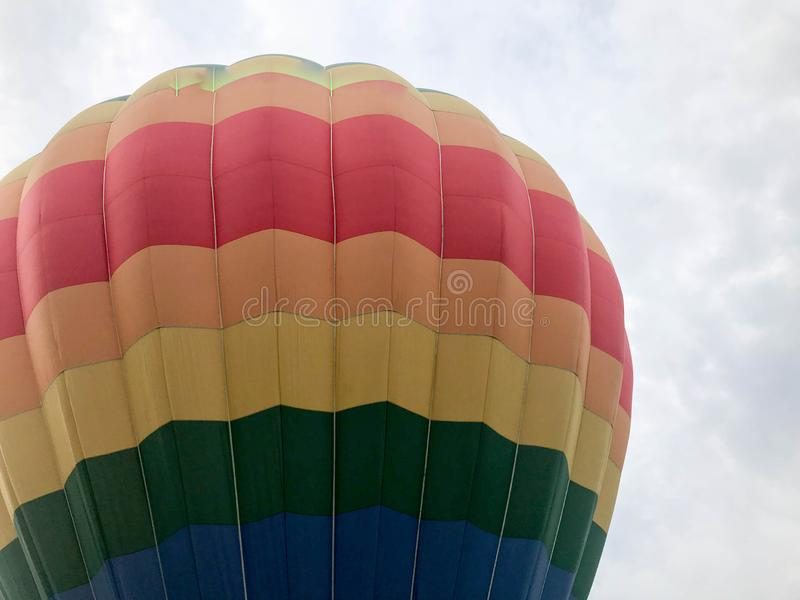 Большой пестротканой яркой круглой воздушный шар летая покрашенный радугой striped striped с корзиной против неба в вечере стоковое фото rf