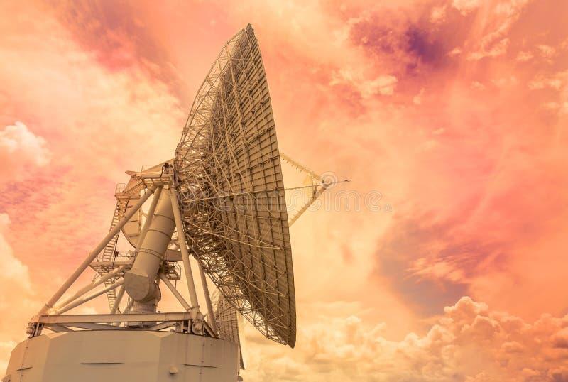 Большой большой поворот спутниковой антенна-тарелки вверх к небу на времени захода солнца стоковые изображения rf