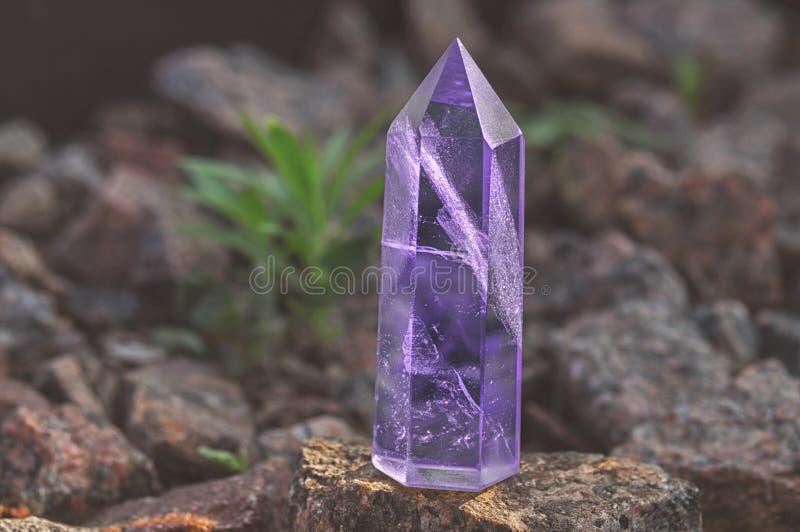 Большой прозрачный мистический граненный кристалл покрашенного аметиста сирени, халцедон на каменном конце-вверх предпосылки Чуде стоковые фото
