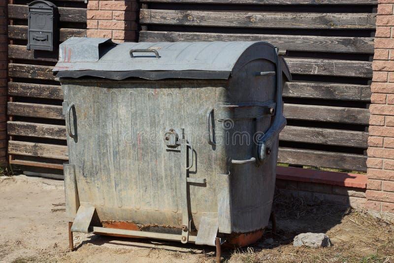 Большой серый мусорный контейнер металла готовит коричневую загородк стоковое фото