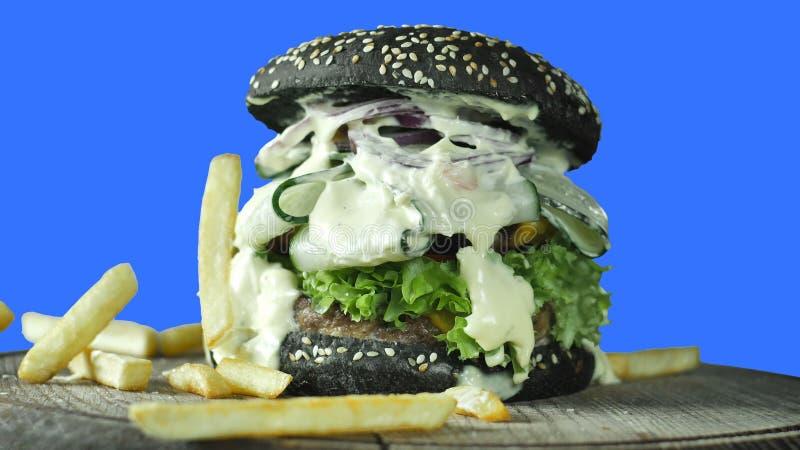 Большой сочный бургер с черной плюшкой взбрызнутой с сезамом с зелеными цветами и пирожком мяса окруженным французским картофелем стоковые изображения rf