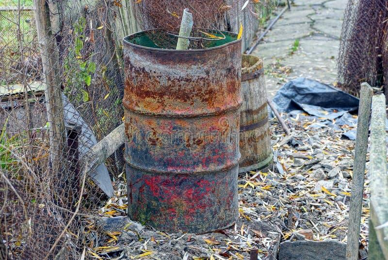 Большой старый ржавый коричневый бочонок с отбросом стоит на улице около загородки стоковая фотография rf