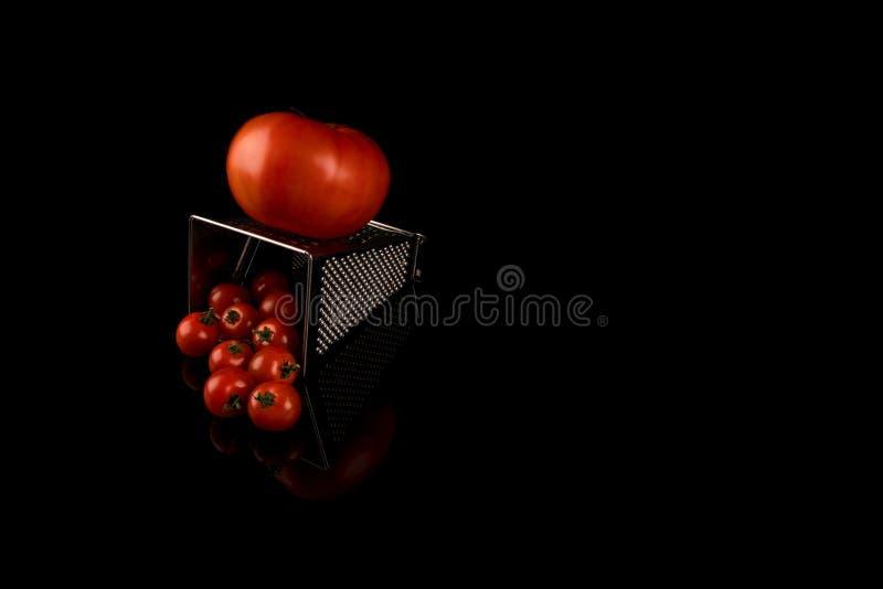 Большой томат заскрежетанный для произведения небольших томатов изолированных на черной предпосылке с отражением r стоковое изображение rf