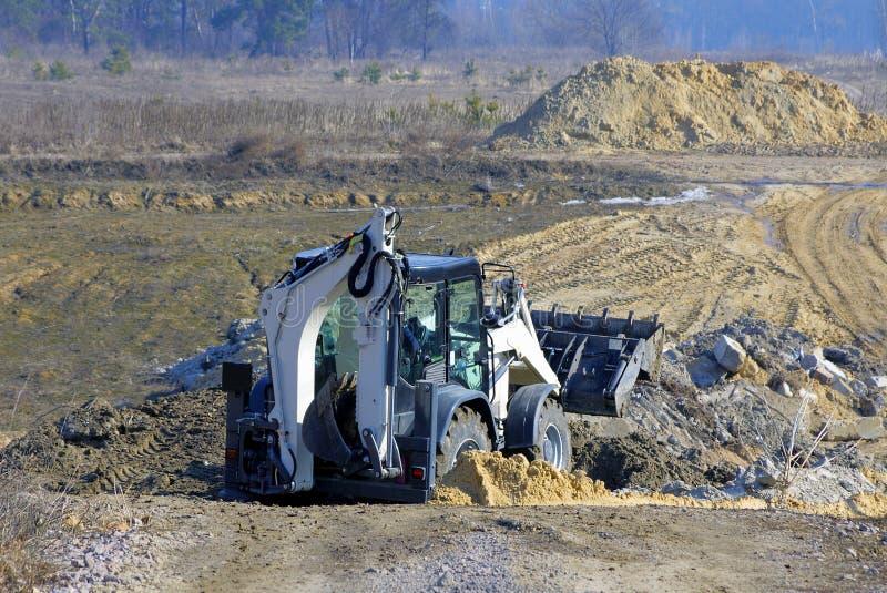 Большой экскаватор выкапывает землю в поле стоковая фотография rf
