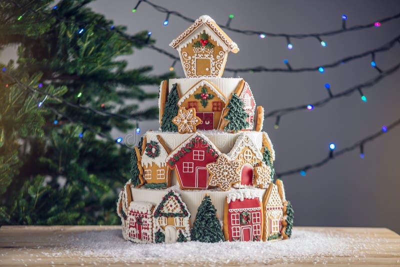 Большой tiered торт рождества украшенный с печеньями пряника и дом на верхней части Дерево и гирлянды на заднем плане стоковые фото