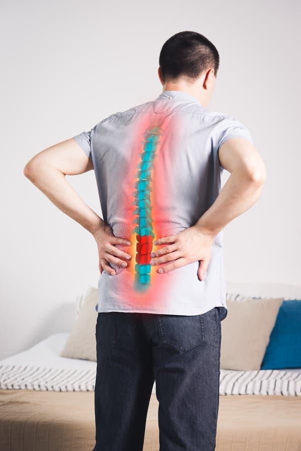 Боль в позвоночнике, человеке с backache дома, ушиб в более низкой задней части стоковые фото