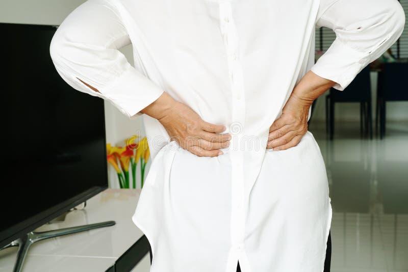 Боль в спине старухи дома, концепция проблемы здоровья стоковая фотография
