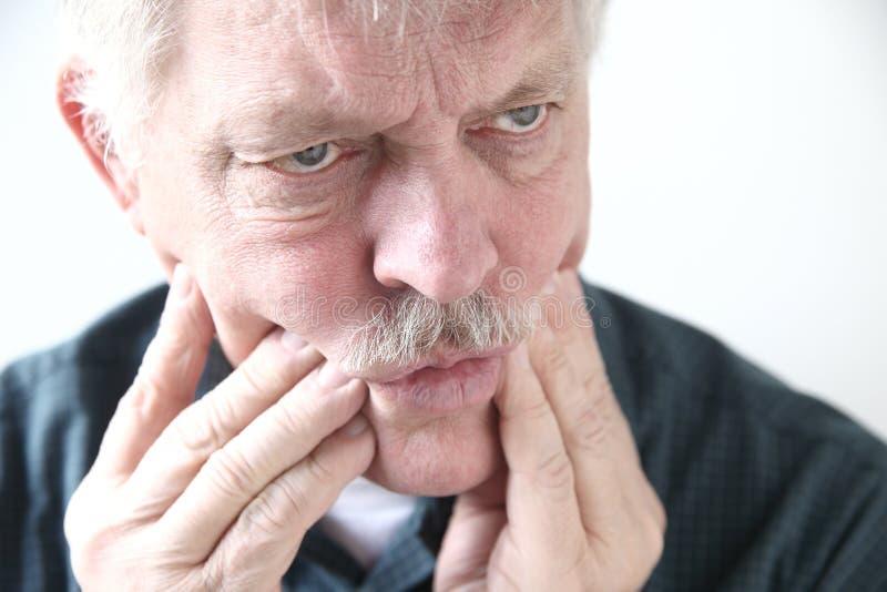 Боль зуба или щеки в более старом человеке стоковое изображение