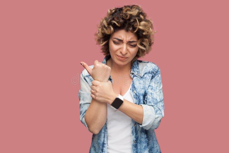 Боль руки или запястья Портрет больной молодой женщины с курчавым стилем причесок в случайном голубом положении и удержании рубаш стоковое фото rf