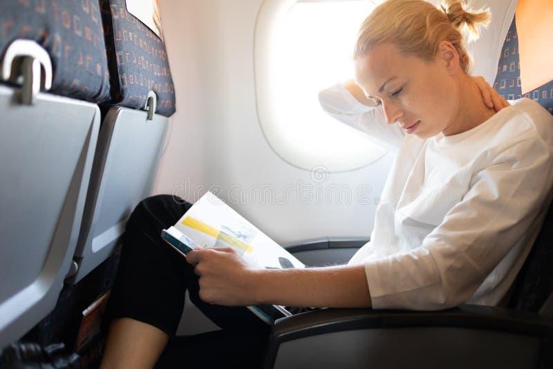 Боль шеи чувства женщины пока читающ в журнале полета на длинном междуконтинентальном полете самолета Женский путешественник стоковые фотографии rf
