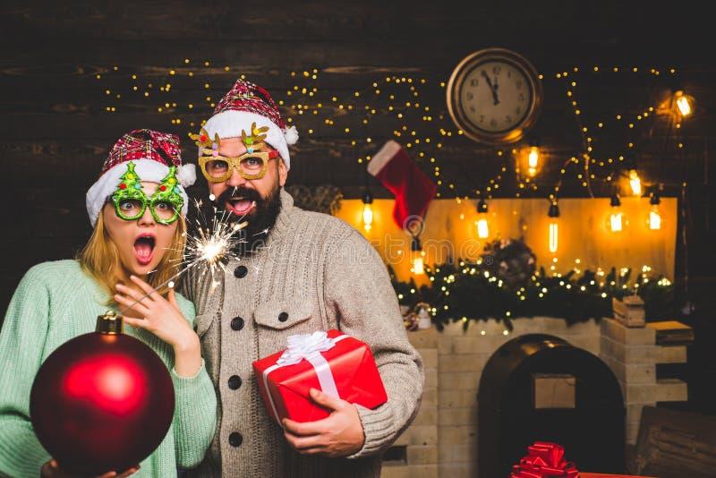 Бомба владением человека рождества Продажа рождества Счастливые пары в шляпе Санта на партии семьи Xmas Партия Нового Года в доме стоковые фото