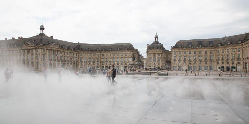 Бордо, Аквитания/Франция - 06 10 2018: потеха игры девушки женщины в фонтане зеркала перед Местом de Ла Фондовой биржей в Бордо, стоковое фото rf