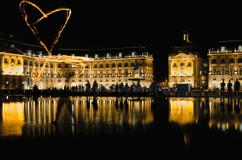 Бордо, Франция - September 15, 2018: Juggler огня рисует сердце огня на зеркале воды в Бордо стоковое фото