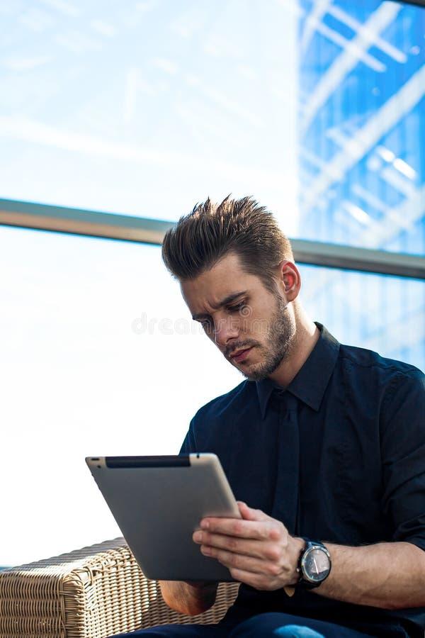Бородатая мужская оплата предпринимателя онлайн через цифровой планшет Банкир используя приложения стоковая фотография