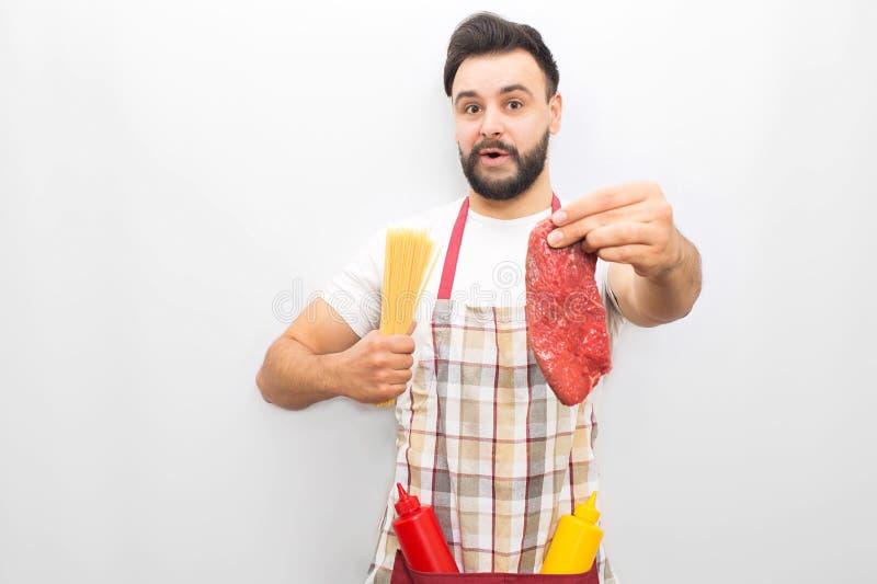 Бородатые главные стойки и интересы Он имеет часть стейка в одной руке и spagetti в другая одной Молодой человек будет в восторге стоковая фотография rf