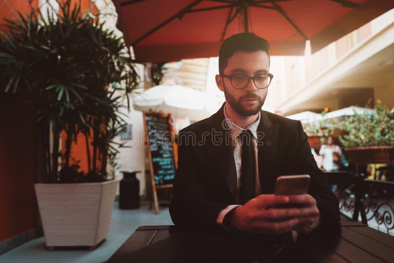 Бородатый бизнесмен послание через мобильный телефон в баре улицы стоковое фото