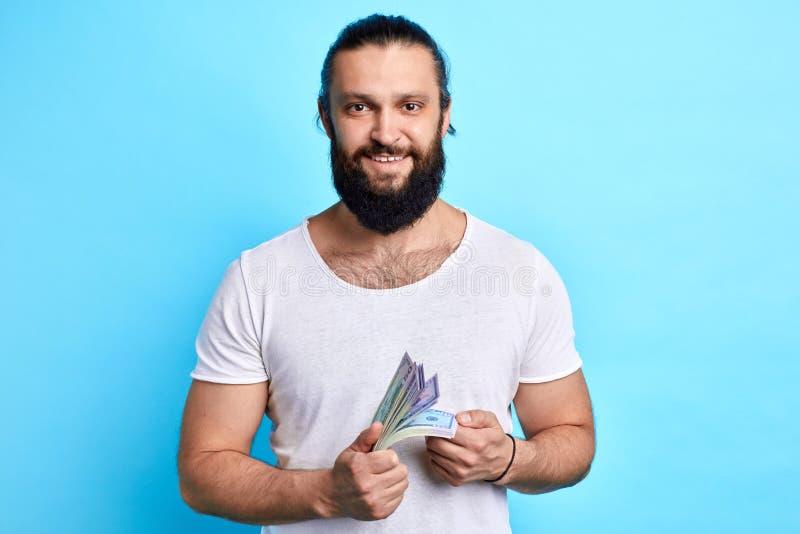 Бородатый бизнесмен с деньгами смотря камеру стоковое фото