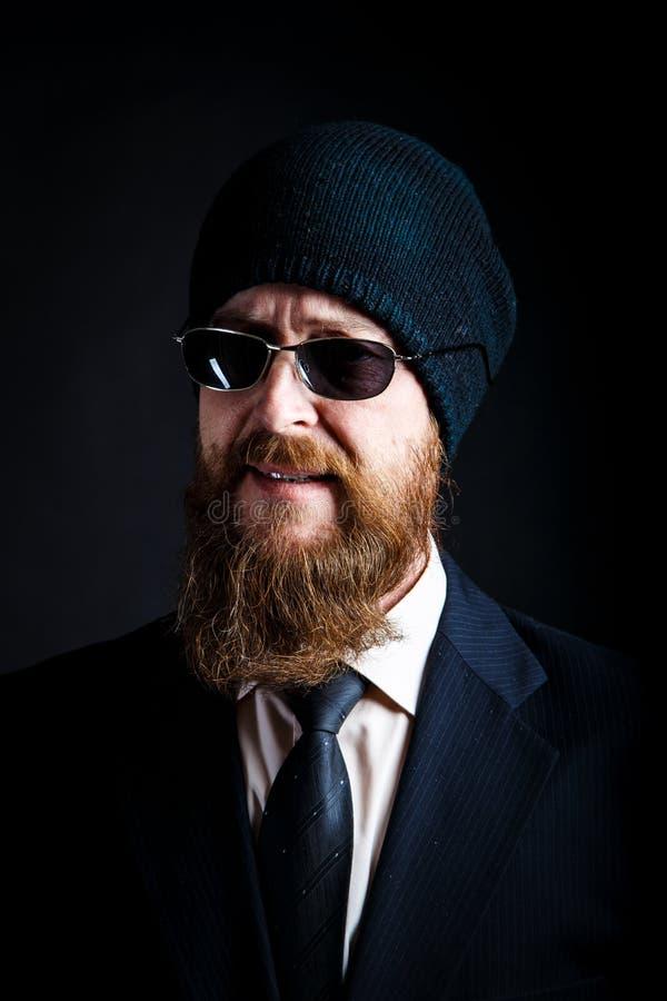 Бородатый бизнесмен человека средн-достигший возраста в черных солнечных очках и черной связанной шляпе смотрит с укоризненым и и стоковое фото